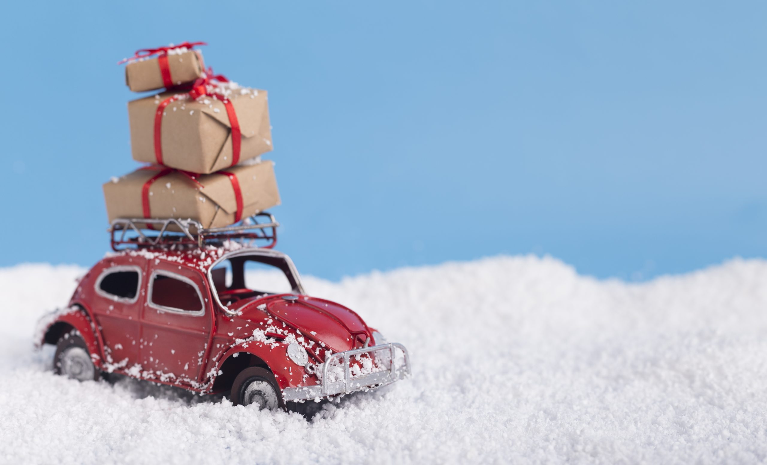 Red toy car with Christmas presents on background